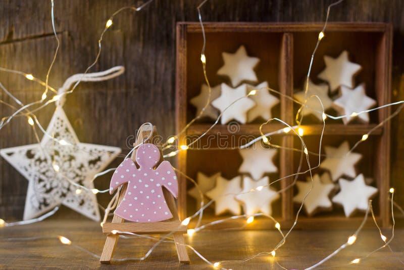 Figurka anioł przeciw drewnianemu pudełku z cynamonowymi gwiazdami zdjęcie stock