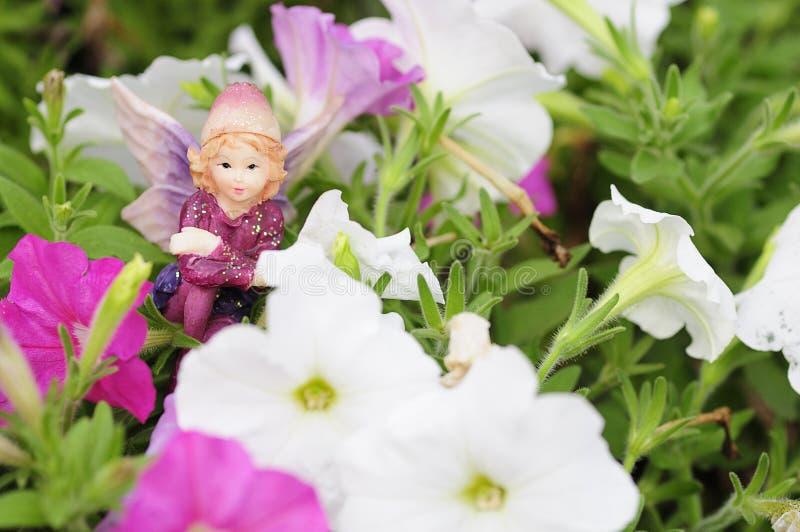 Figurka czarodziejka wystawiająca wśród bielu i menchii petuni fotografia royalty free