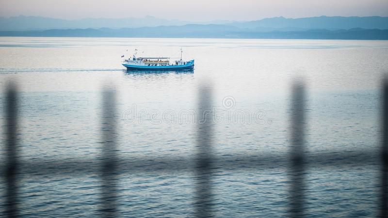 A fihing boat on the calm waters of the Gulf of Trieste. A singular fishing boat on the calm waters of the Gulf of Trieste taking in the setting sun and the pink stock image