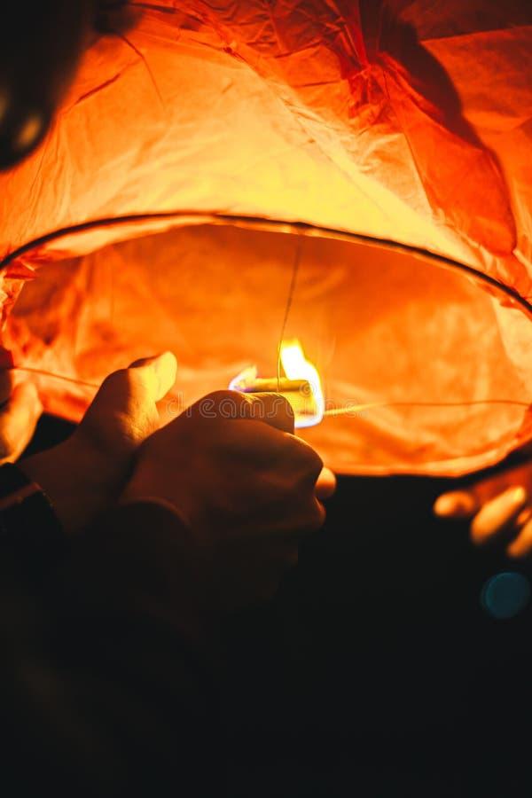 Fija el fuego a una linterna de papel divina antes de lanzar en el cielo oscuro de la tarde imagen de archivo