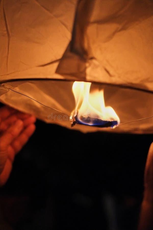 Fija el fuego a una linterna de papel divina antes de lanzar en el cielo oscuro de la tarde, creando una atmósfera romántica fotografía de archivo libre de regalías