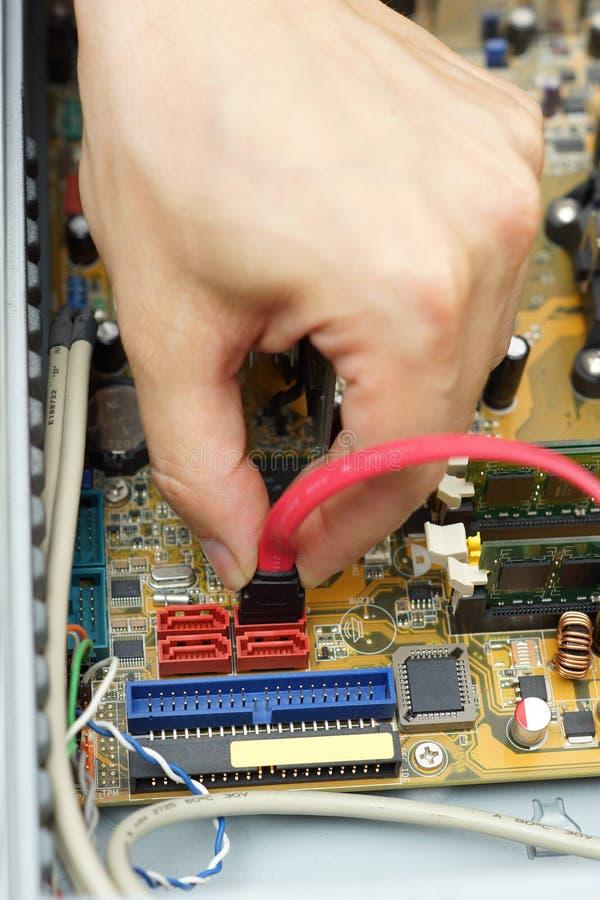 Fijación del reparador del ordenador el cable de la unidad de disco duro al motherboa imágenes de archivo libres de regalías