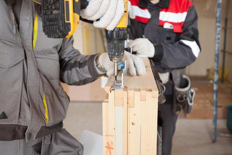 Fijación del trabajador del albañil de la construcción el metal de la ventana que cabe al tragaluz imágenes de archivo libres de regalías