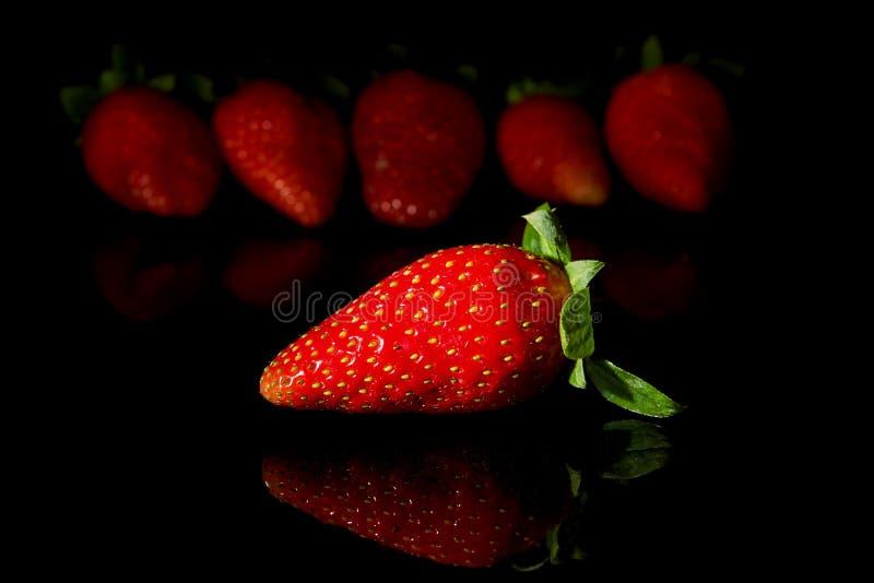 Fijado de las fresas con la reflexión en negro foto de archivo