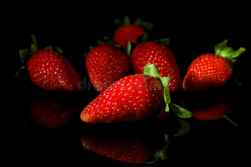 Fijado de las fresas con la reflexión en negro fotos de archivo