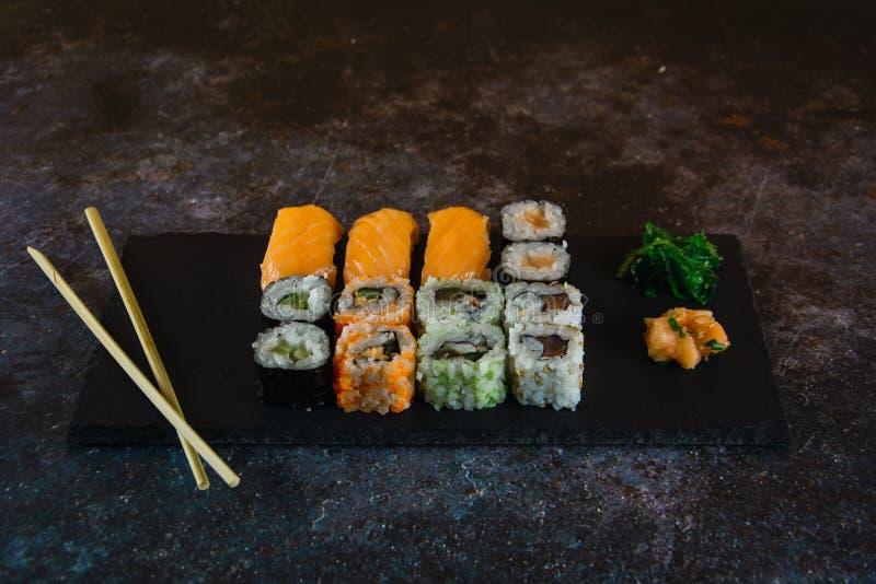 Fijado del sushi del sashimi y de los rollos de sushi sirvió en la pizarra de piedra acompañada con la salsa y la alga marina tra imagen de archivo