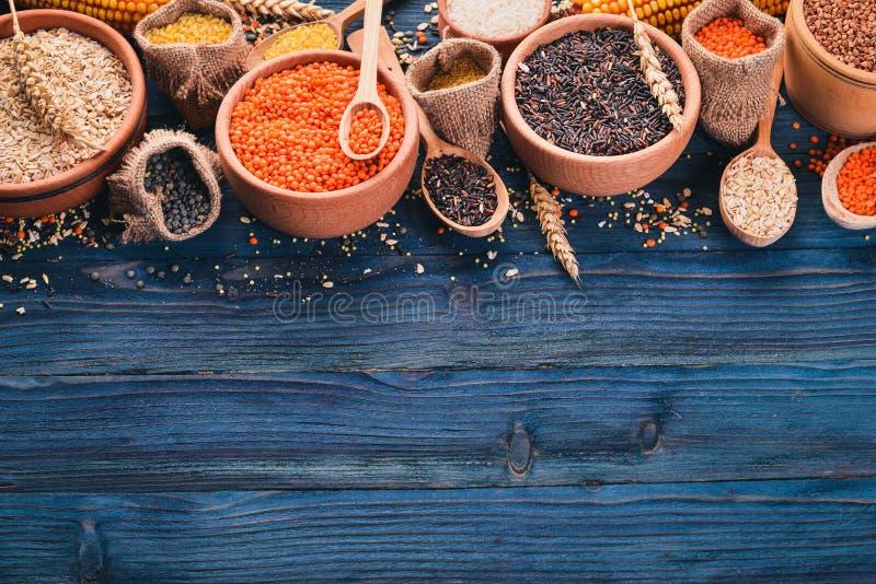 Fije de avenas mondadas y de granos Alforfón, lentejas, arroz, mijo, cebada, maíz, arroz negro En un fondo de madera azul fotos de archivo