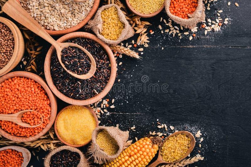 Fije de avenas mondadas y de granos Alforfón, lentejas, arroz, mijo, cebada, maíz, arroz negro En un fondo negro foto de archivo