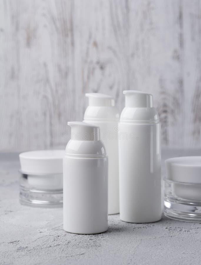 Fije de botellas poner crema cosméticas en fondo gris foto de archivo libre de regalías