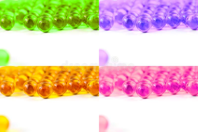 Fije de cápsulas esféricas coloreadas de la bola de foco selectivo del aceite de pescado aislado en el fondo blanco imagen de archivo