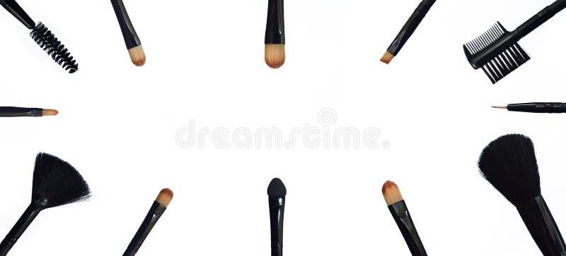Fije de cepillos del maquillaje en fondo compuesto coloreado fotografía de archivo libre de regalías