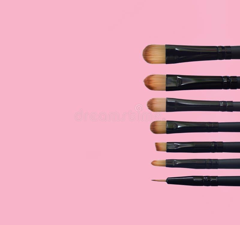 Fije de cepillos del maquillaje en fondo compuesto coloreado imagenes de archivo
