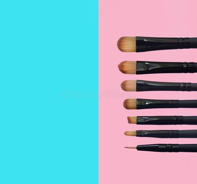 Fije de cepillos del maquillaje en fondo compuesto coloreado imagen de archivo
