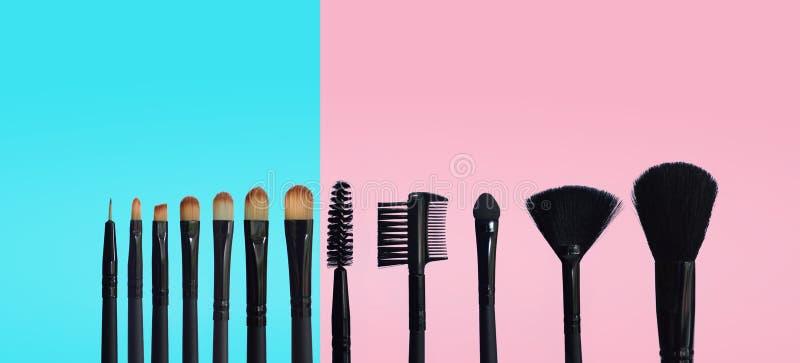 Fije de cepillos del maquillaje en fondo compuesto coloreado foto de archivo libre de regalías