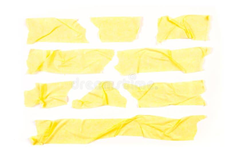 Fije de cintas amarillas en el fondo blanco Cinta pegajosa amarilla rasgada de tamaño horizontal y diverso, pedazos adhesivos imágenes de archivo libres de regalías