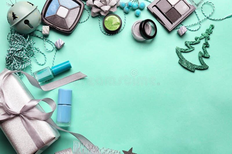 Fije de cosméticos con el regalo de Navidad y de decoraciones en fondo del color foto de archivo libre de regalías