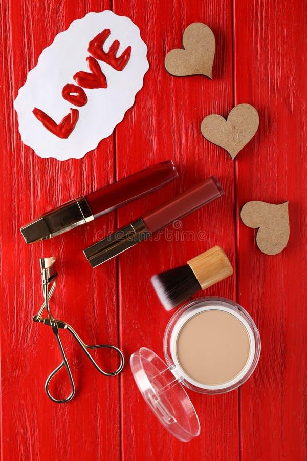Fije de cosméticos con la palabra AMOR en fondo de madera del color imagen de archivo