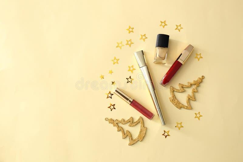 Fije de cosméticos con las decoraciones de la Navidad en fondo del color imágenes de archivo libres de regalías