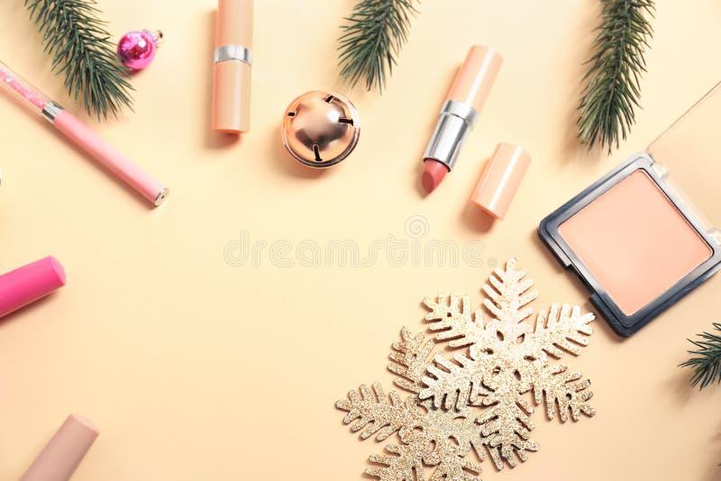Fije de cosméticos con las decoraciones de la Navidad en fondo del color fotografía de archivo libre de regalías