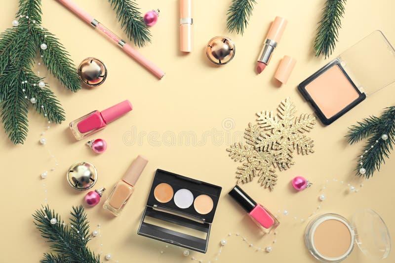 Fije de cosméticos con las decoraciones de la Navidad en fondo del color foto de archivo