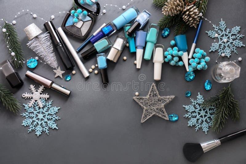 Fije de cosméticos con las decoraciones de la Navidad en fondo gris imagenes de archivo