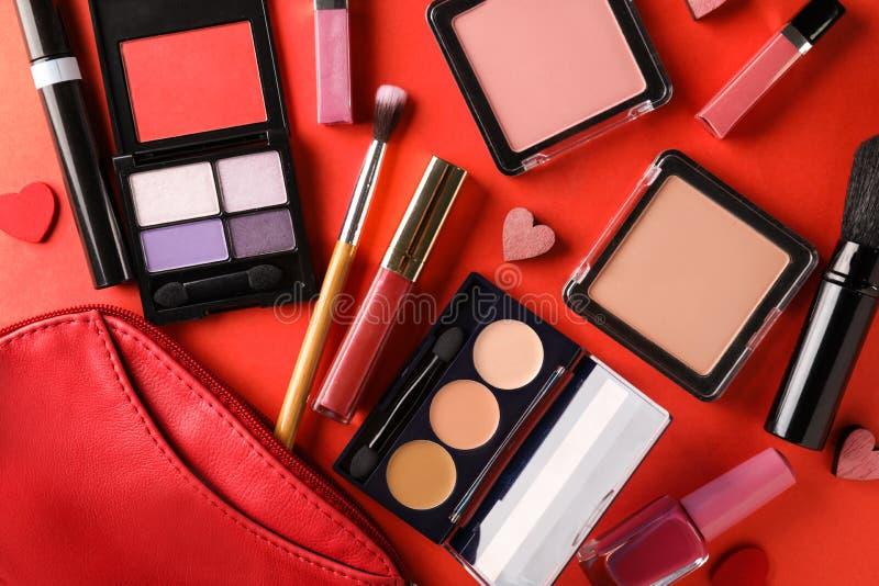 Fije de cosméticos con los pequeños corazones y de bolso en fondo del color fotografía de archivo