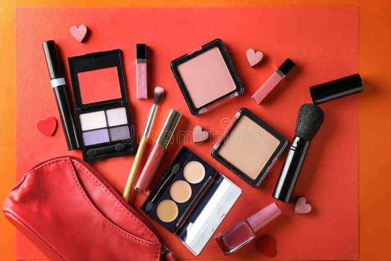 Fije de cosméticos con los pequeños corazones y de bolso en fondo del color fotos de archivo libres de regalías
