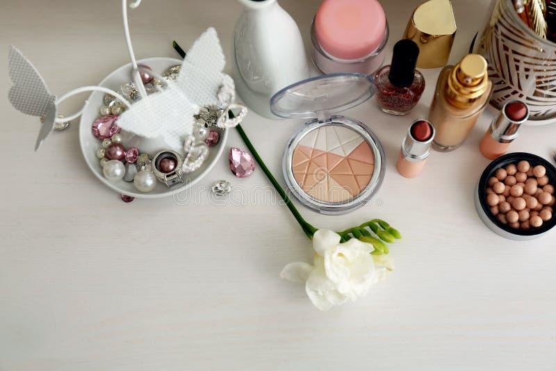 Fije de cosméticos decorativos con joyería en la tabla blanca fotografía de archivo