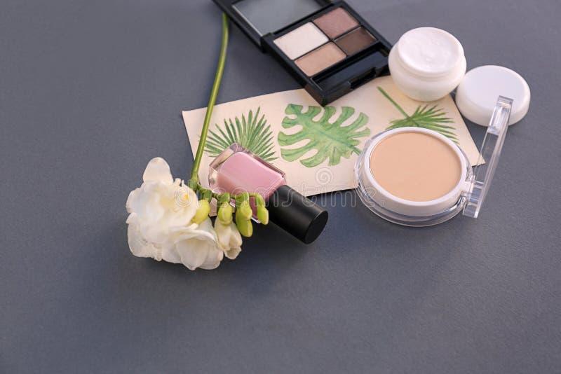 Fije de cosméticos decorativos con las flores en fondo gris imagenes de archivo