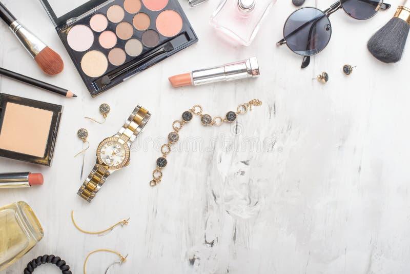 Fije de cosm?ticos, de herramientas del maquillaje y de accesorios profesionales en un fondo de m?rmol blanco con el espacio de l fotos de archivo libres de regalías