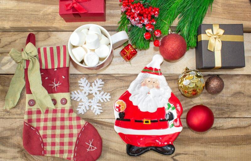 Fije de decoraciones de la Navidad una placa bajo la forma de Papá Noel, un calcetín para los regalos, una taza con las melcochas fotos de archivo