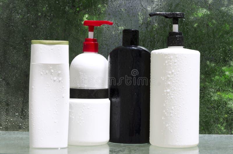 Fije de diversas botellas de productos cosméticos en el estante de cristal Diverso de los productos para el cuidado del cabello fotografía de archivo
