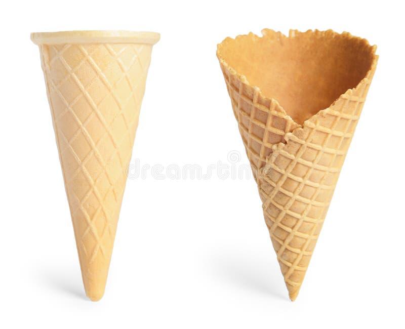 Fije de diversos conos de helado curruscantes vacíos de la oblea en el fondo blanco imagenes de archivo