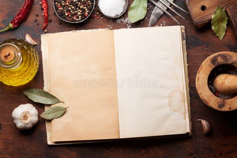 Fije de diversos especias e hierbas y libro de cocina foto de archivo