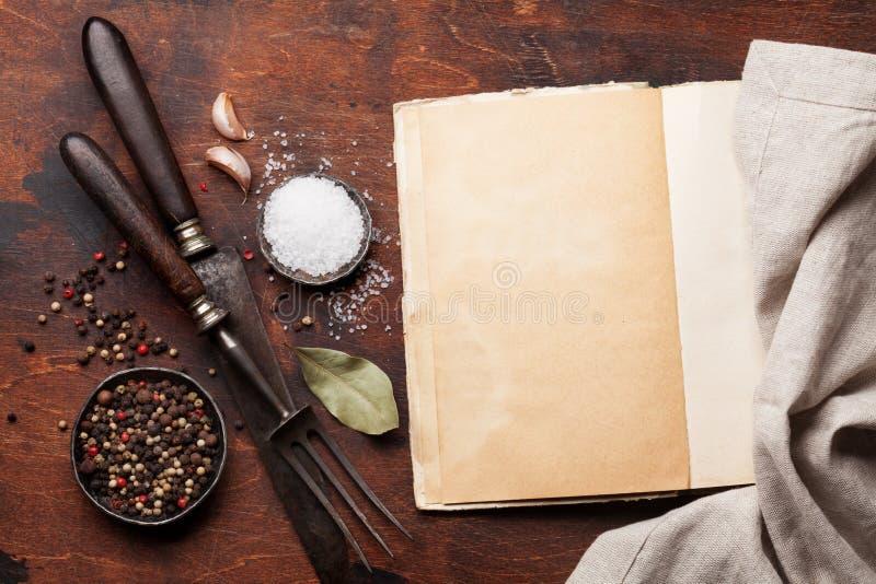 Fije de diversos especias e hierbas y libro de cocina imagen de archivo
