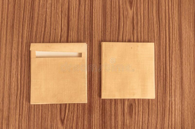 Fije de frente del sobre de dos Brown y detrás aislado en fondo de madera del suelo de parqué de la tabla Espacio en blanco de la foto de archivo