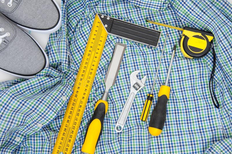 Fije de herramientas amarillas en la camisa a cuadros y la opinión superior de las zapatillas de deporte concepto puesto plano de fotografía de archivo