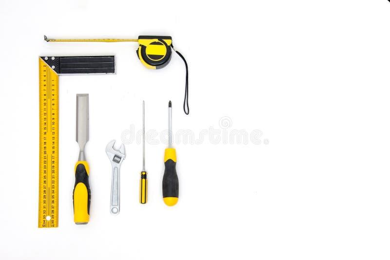 Fije de herramientas amarillas en la opinión superior del fondo blanco tabla de funcionamiento del carpintero carpintería y endec imagen de archivo