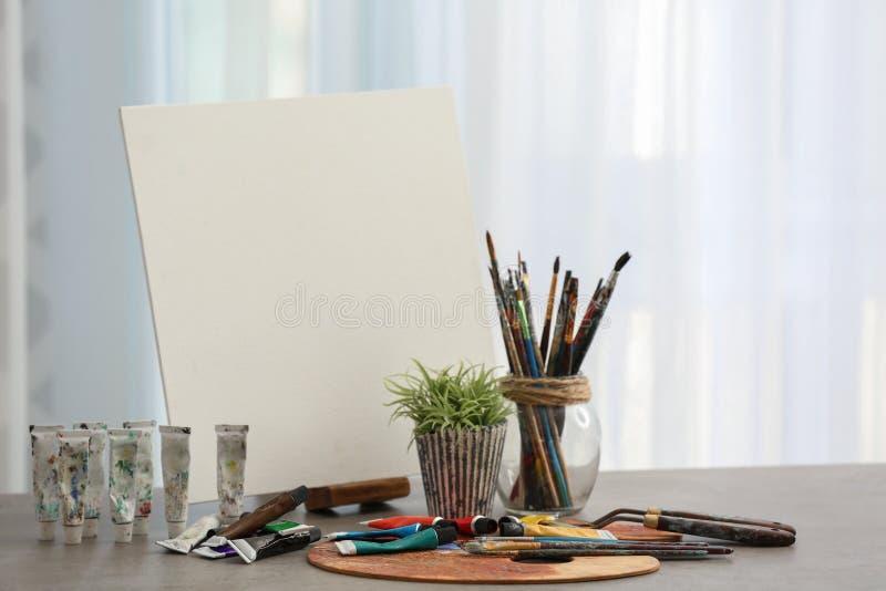 Fije de herramientas y de pinturas con la lona del artista profesional en la tabla en taller imágenes de archivo libres de regalías