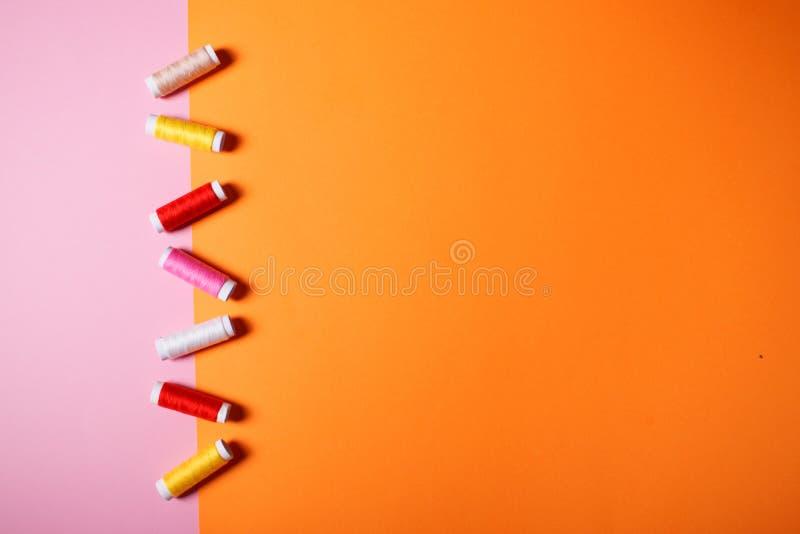 Fije de hilos de coser coloridos en fondo brillante imagenes de archivo