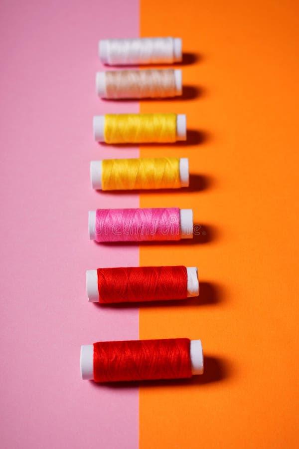 Fije de hilos de coser coloridos en fondo brillante fotos de archivo