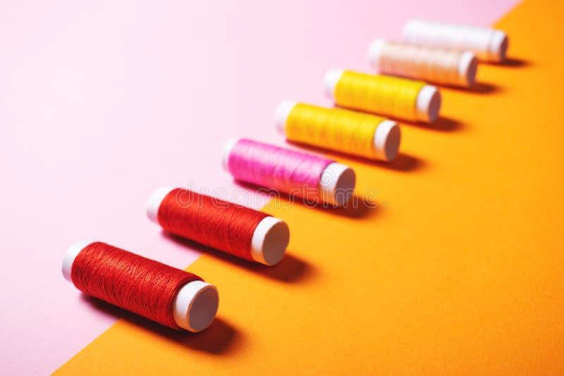 Fije de hilos de coser coloridos en fondo brillante foto de archivo libre de regalías