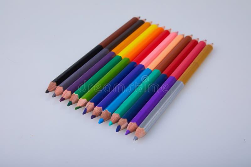 Fije de lápices coloreados dobles en el fondo blanco imagen de archivo