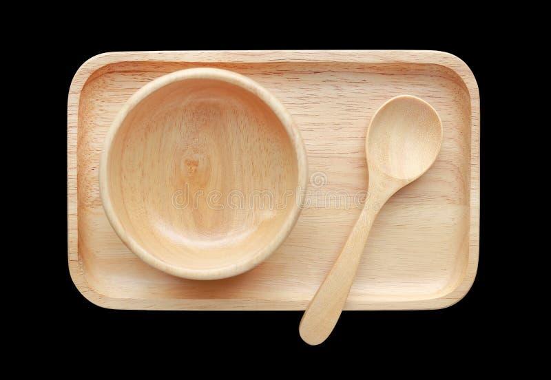 Fije de la bandeja, del cuenco de madera y de la cuchara aislados en fondo negro Visión superior foto de archivo