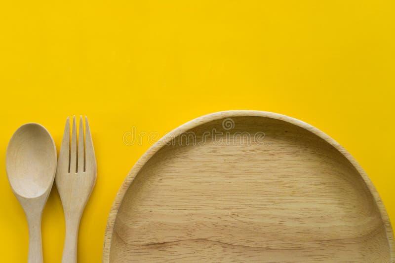 Fije de la bifurcación, de la cuchara y de la madera del plato con el fondo amarillo foto de archivo libre de regalías