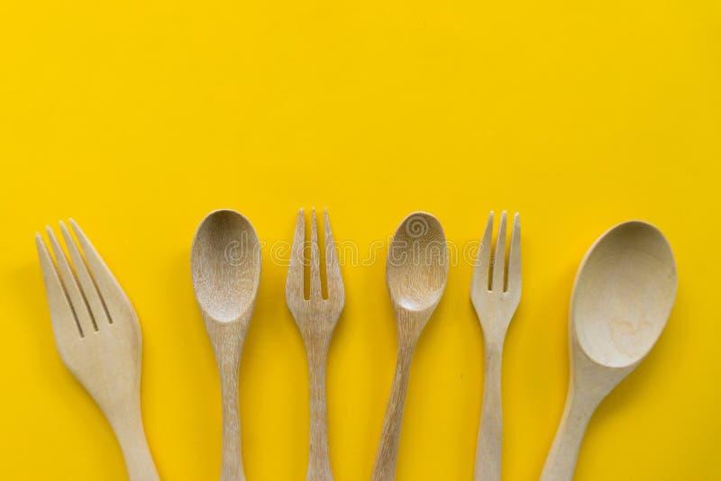 Fije de la bifurcaci?n, de la cuchara y de la madera del plato con el fondo amarillo imagenes de archivo