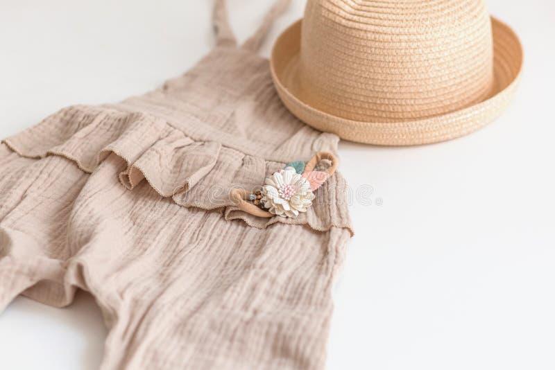Fije de la ropa de los niños del verano para la muchacha Aislado, espacio de la copia Traje del mameluco, sombrero de paja y acce fotos de archivo