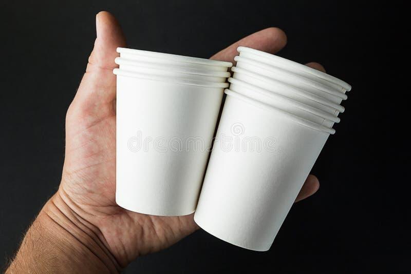 Fije de la taza para llevar de café, de té o de jugo a disposición en el fondo negro, maqueta imágenes de archivo libres de regalías