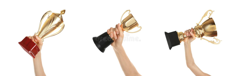 Fije de las mujeres que sostienen diversas tazas brillantes del trofeo del oro imagen de archivo libre de regalías