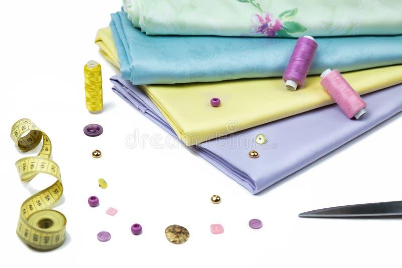 Fije de los accesorios de costura un sistema de los botones, telas, hilos del color en el fondo blanco fotografía de archivo libre de regalías